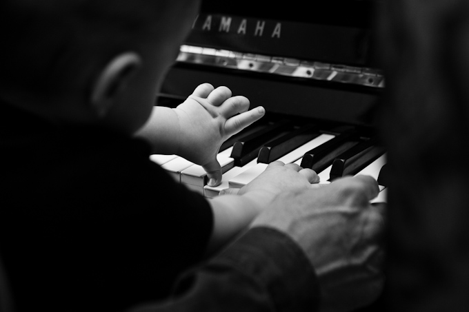 Baby playing on the piano with his father